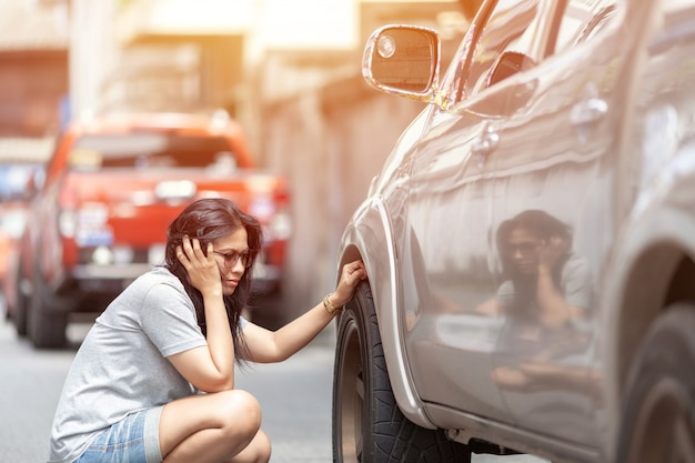 Унылая азиатская молодая красивая женщина при потревоженное усиленное выражение лица смотря вниз в колесах автомобиля с космосом экземпляра