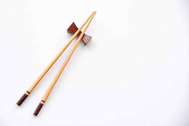 白い背景に木製の箸スペースをコピーします。