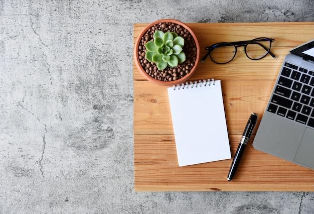 白紙の紙、多肉植物とコピースペースを持つ木製のテーブルの上にペン
