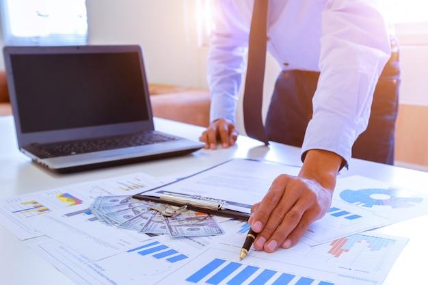Молодой предприниматель, проведение перо, указывая на график и диаграммы.