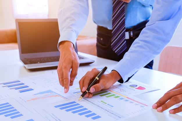 Молодой предприниматель, проведение перо, указывая на график и диаграммы в офисе.