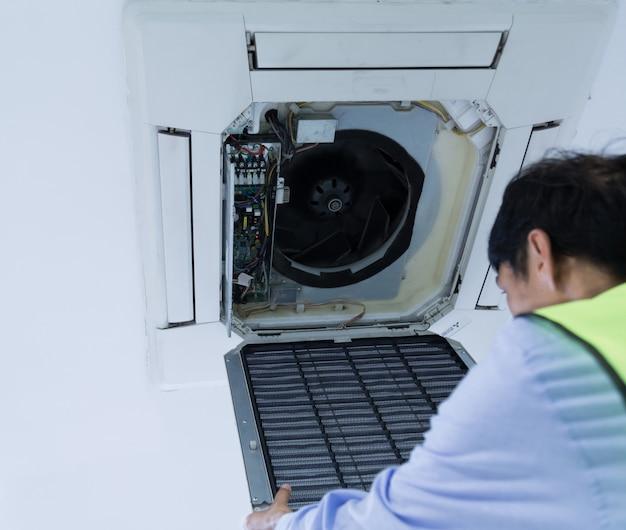 壁にエアコンを修復する技術者。