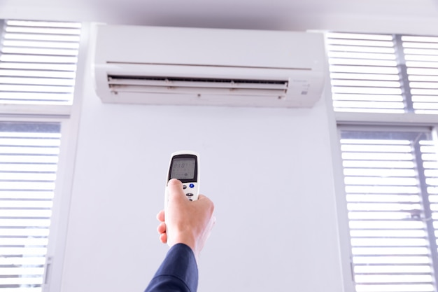 リモートコントローラを操作する人と室内のリモコン付きエアコン、。