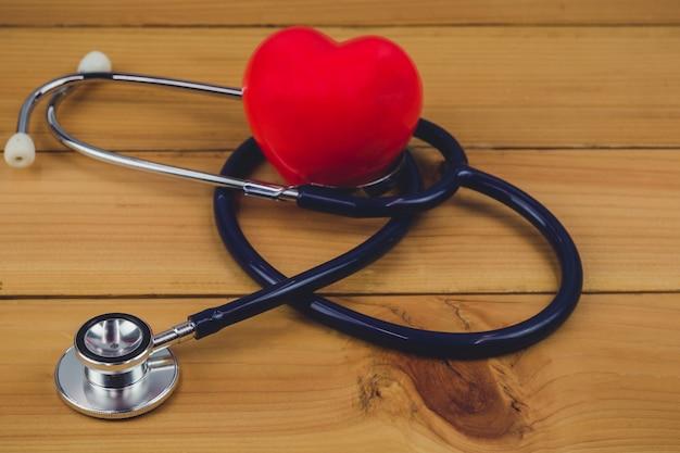 赤いハートと古い木製のテーブルに聴診器を閉じる
