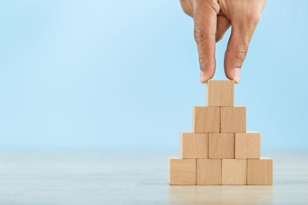 ビジネスマンの手を閉じる、ステップに木製のブロックを積み重ねる