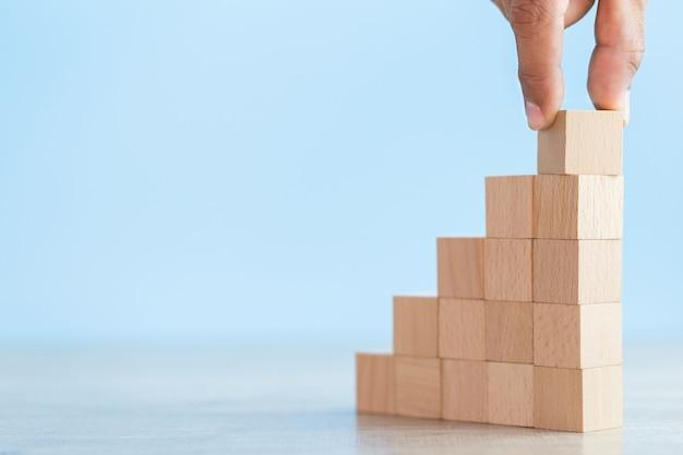Рука ближе к рукам бизнесменов, укладка деревянных блоков в ступеньки, концепция успеха роста бизнеса
