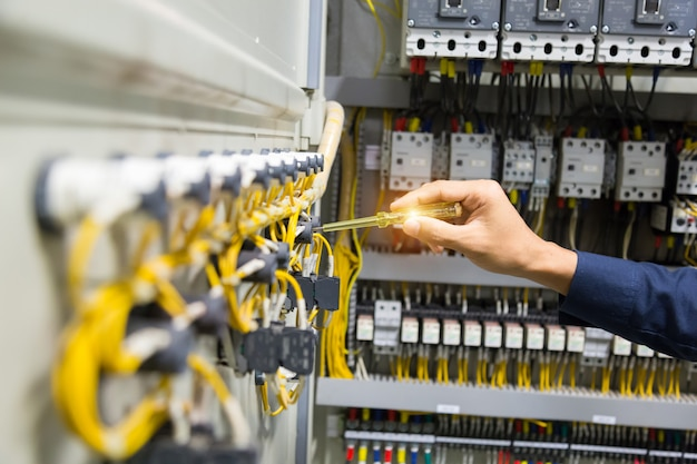 電気技師はコントロールパネルで現在の電気をテストする手。