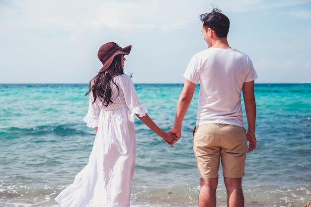 カップルがバックグラウンドで美しい夕日とビーチでキスします。