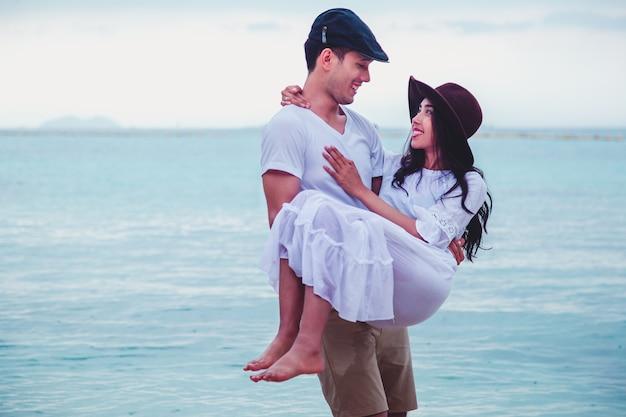 美しい夕日を楽しんで幸せなロマンチックな若いカップルは、ビーチの上を歩きます。旅行休暇退職ライフスタイルのコンセプト