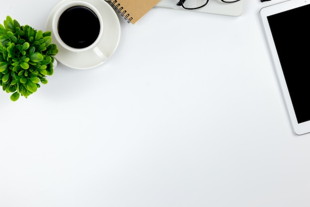 空白のノートブックタブレットとスマートフォンを持つオフィスのワークスペースを持つ事務机の平面図