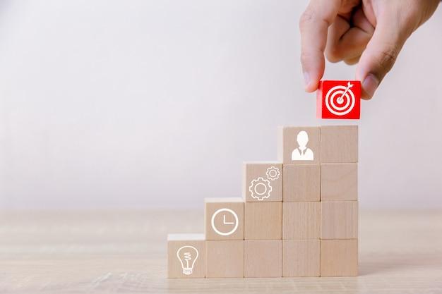 木製の階段のブロックを敷設するビジネスマン。成功への事業のサービスコンセプト事業戦略の立案市場での勝利へ。