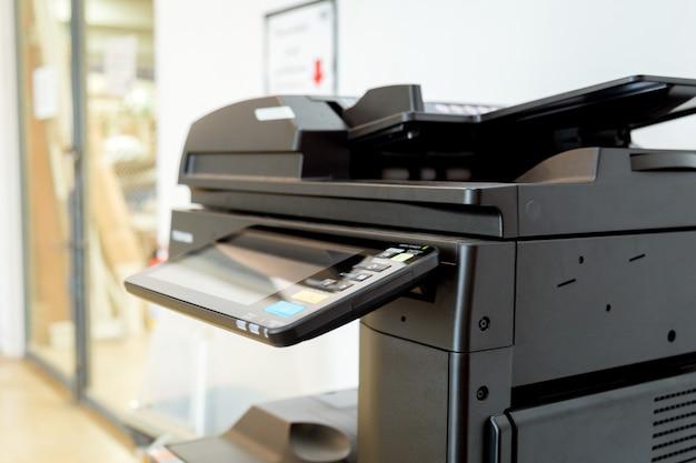 Закройте вверх по бумажным листам на принтере в комнате офиса.