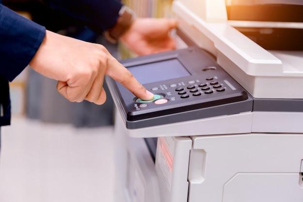 クローズアップ商務人プリンターのパネル上の手でボタンを押す、プリンタースキャナーレーザーオフィスコピー機用品スタートコンセプト。