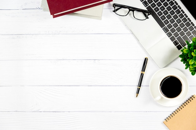 オフィスのワークスペース、空白のノートブックを含む木製の白い机および他の事務用品