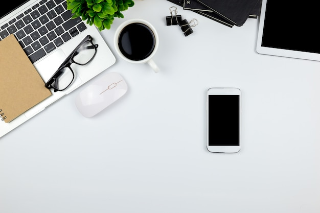 タブレットと空の空白の画面を持つスマートフォンが付いているオフィスのワークスペース。