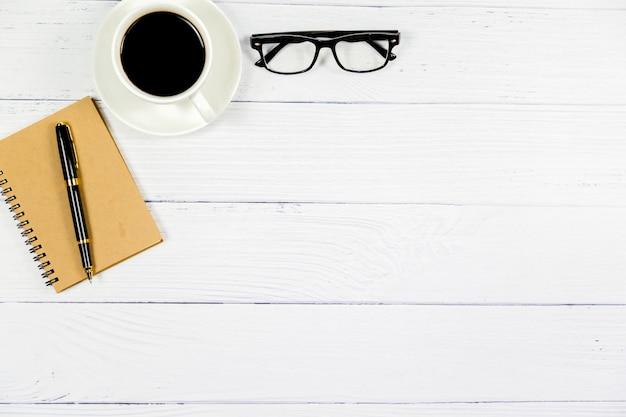 オフィス、コーヒー、グラス、ペン、ビジネスコンセプトと木製の白い机の上から見る。