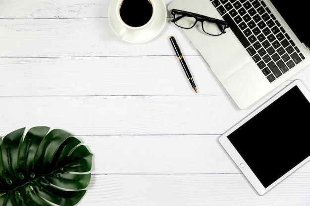 オフィスのワークスペース、空白のノートブックおよび他の事務用品の木製白い机、コピースペース平面図。