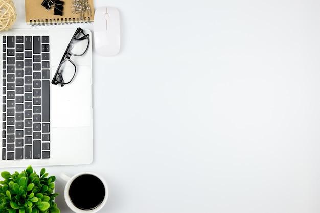 空白のノートブックとコピースペースを持つ他の事務用品とオフィスのワークスペースを持つ事務机の平面図です。