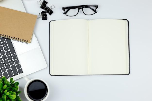 空白のノートブックとコピースペースを持つ他の事務用品との本のオフィスのワークスペースを持つ事務机の平面図です。