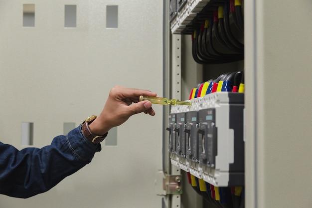電気キャビネットの制御における電力線の電圧と電流を測定する電気技師作業テスタ