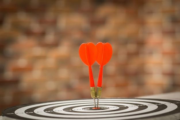 赤いダーツターゲット矢印でブルズアイにぶつかる、ターゲットマーケティングとビジネスの成功