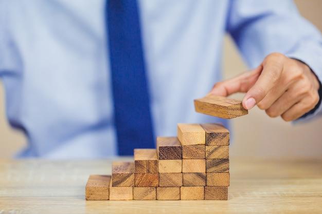 Вытаскивание руки или размещение деревянного блока на башне, план и стратегия в бизнесе