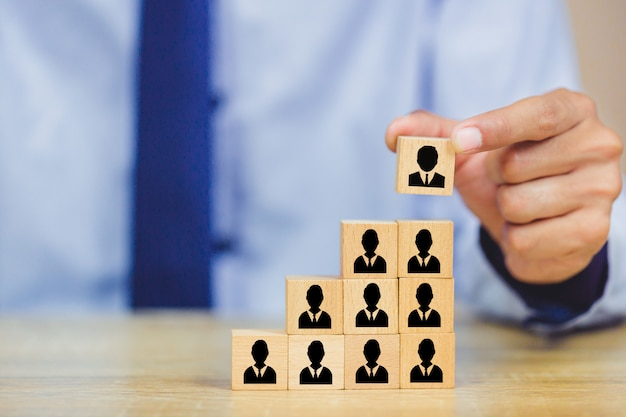 Рука, укладка деревянных блоков с иконой бизнес человеческих ресурсов