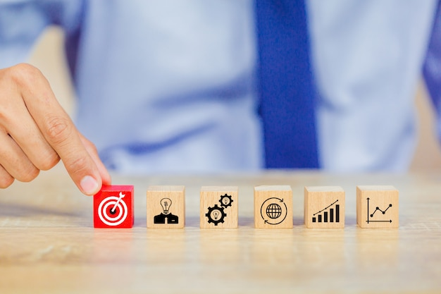 ビジネスマンの手がターゲットの成功の概念を上にウッドキューブブロックを置くこと。