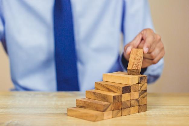 手の引き出しやタワー、ビジネスの計画と戦略の上に木のブロックを配置