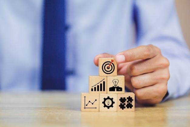 Рука бизнесмена аранжируя деревянный блок с стратегией цели цели значка.