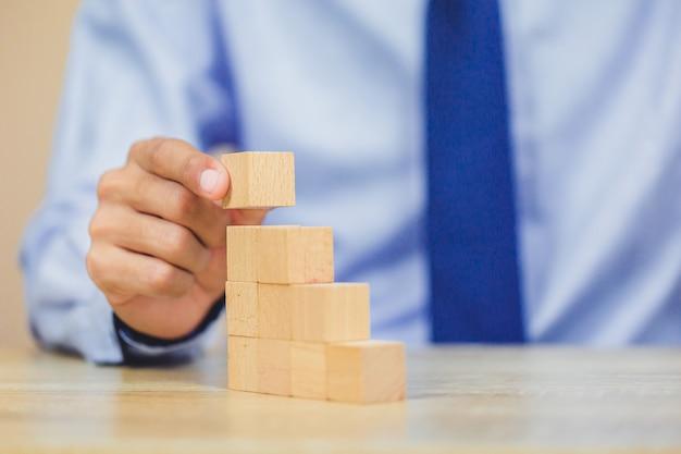 ステップに木製のブロックを積み重ねて、ビジネスマンの手を閉じます。