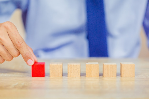 ステップに木製のブロックを積み重ねるビジネスマンの手。