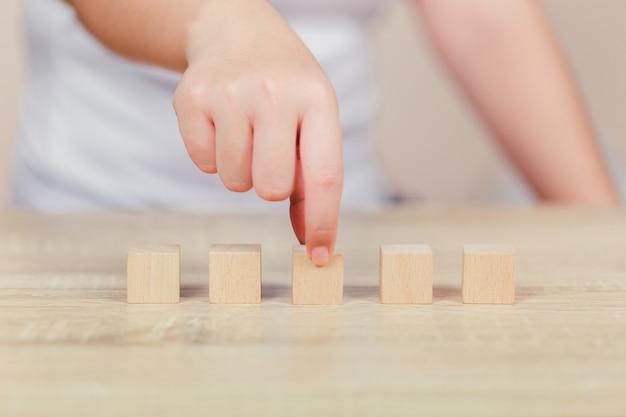 ステップに木製のブロックを積み重ねる女性の手。