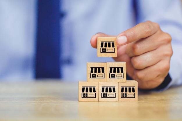ビジネスマンの手は、フランチャイズマーケティングと木材のブログを選択します。