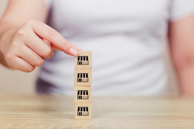 Рука женщины выбирает деревянный блог с маркетингом франшизы.