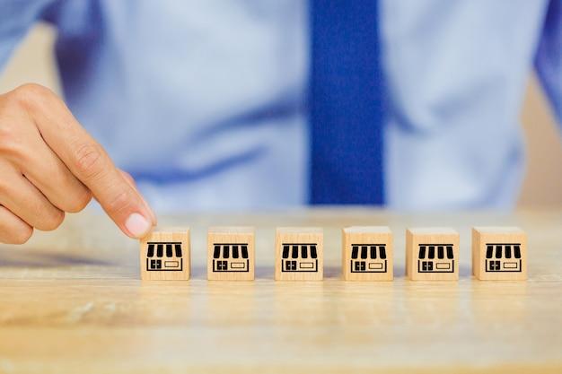 Рука бизнесмена выбирает деревянный блог с маркетингом франшизы.