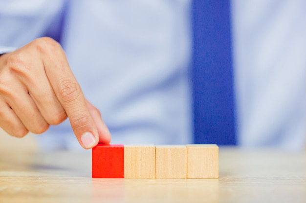 木製のブロックを積み重ねて、ビジネスマンの手をより近く。