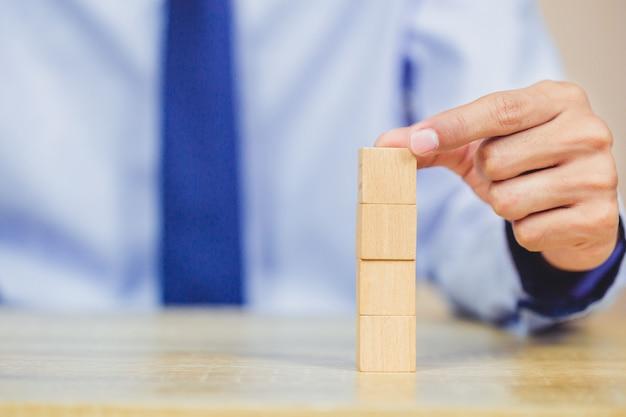 木製のブロックを積み重ねるビジネスマンの手。