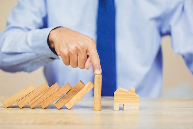 実業家の手を止めることは、家に落ちるから木製のブロックを危険にさらします。