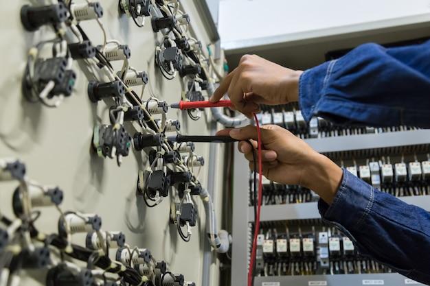 電気技師のエンジニアは、電気キャビネット制御の電力電線の電圧と電流を測定するテスターを作業します。