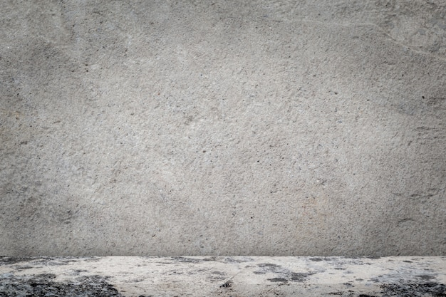 空の灰色のコンクリートの壁の背景を持つコンクリートの床。