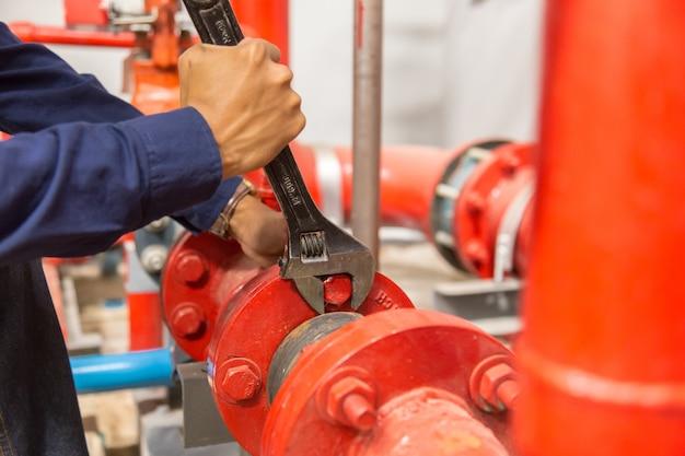 Сантехник ремонтирует и выполняет обслуживание больших водопроводных труб.