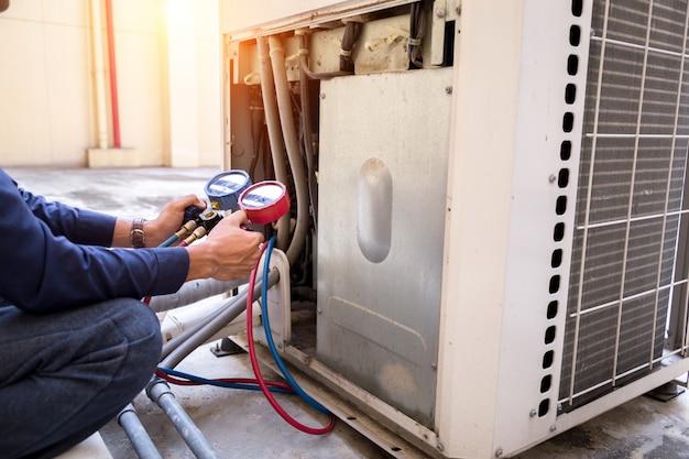 技術者は、エアコンを充填するためのエアコン測定機器をチェックしています。