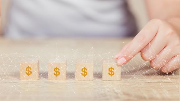 Рука женщины аранжируя деревянный блок с финансами роста доллара денег значка и концепцией вклада.