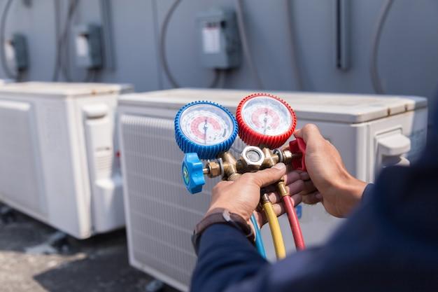 技術者は空調機を点検し、空調機を充填するための機器を測定している。