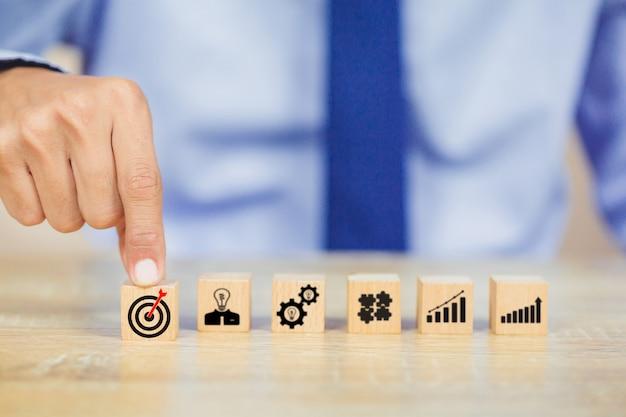 アイコンのターゲットとウッドブロックを配置するビジネスマン手。成功のコンセプト。