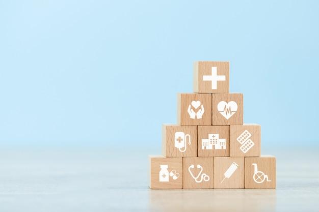 健康保険のコンセプト。アイコン医療医療とスタッキングウッドブロック。