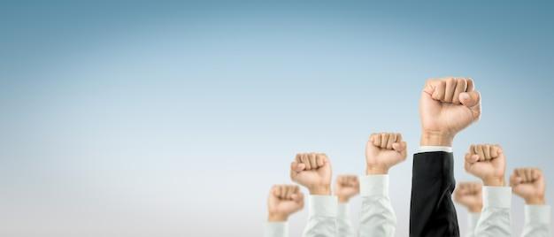 ビジネスマンは、組織のお祝いに勝つために手を挙げました。ビジネスの概念は成功に向けられています。