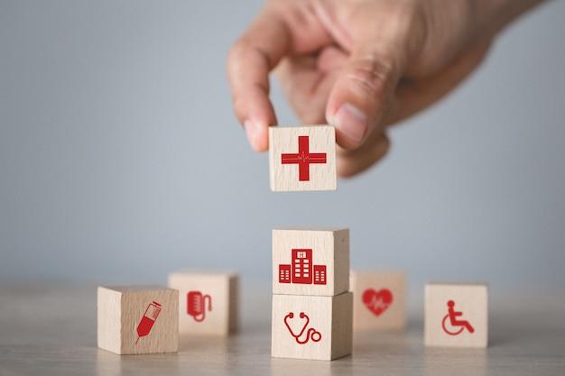健康保険の概念、アイコン医療医療とウッドブロックのスタッキングを配置する手。