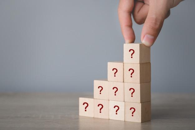 Вручите аранжировать деревянный блок штабелируя с вопросительным знаком значка, думая с концепцией вопросительного знака.